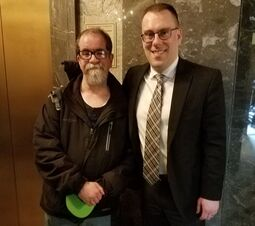 2 Caucasian men stand side by side in front of a elevator at the state capitol.